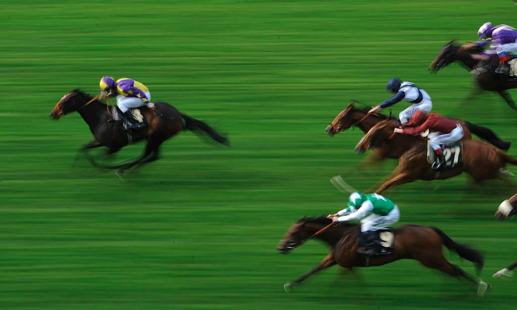 An aerial shot of a horse race where one horse has pulled away significantly from the pack.